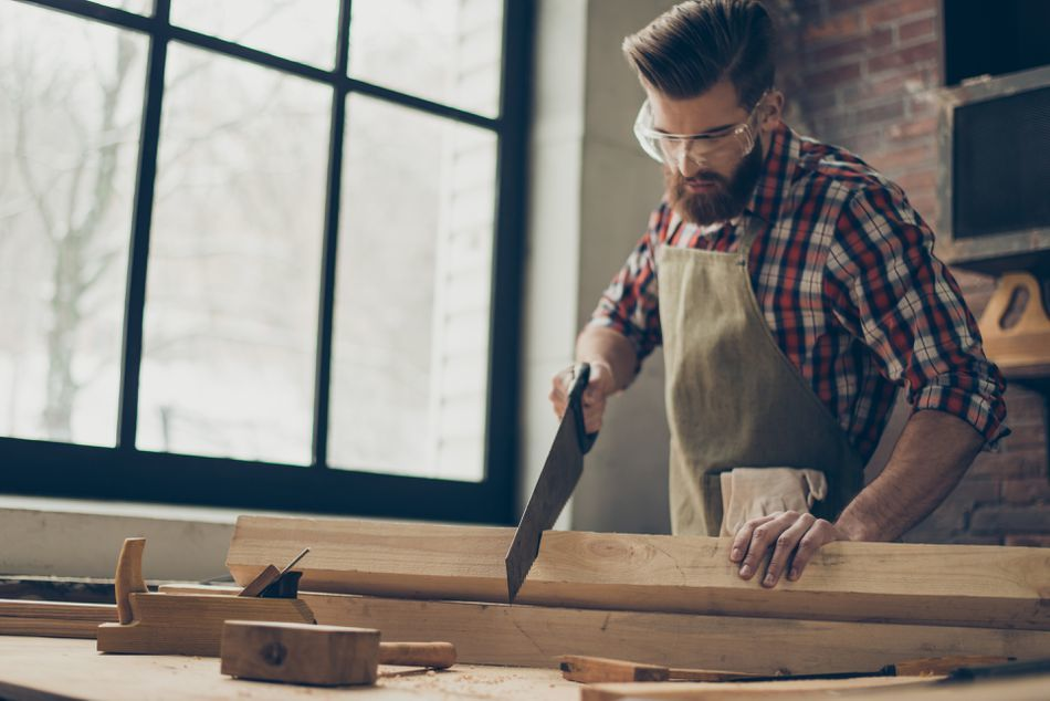 young-stylish-cabinet-maker-with--glasses-and-hairstyle--strong--handsome-craftsman-holding-saw-and-wood-blank-at-workplace-944613244-5af9afc2a18d9e003c17040c